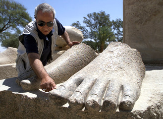 AN EGYPTIAN ANTIQUITIES EXPERT EXAMINES A RECENTLY EXCAVATED FRAGMENTOF A STATUE IN LUXOR'S WEST BANK.