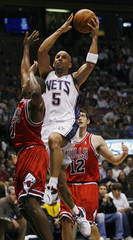 New Jersey Nets Kidd scores against Chicago Bulls Duhon and Hinrich in first quarter of NBA basketball game in East Rutherford