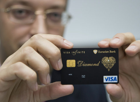 Executive Director of Eurasian Bank shows a new VISA card encrusted with diamond and laced with an elaborate gold pattern in Almaty