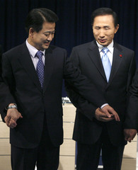 Lee Myung-bak of the conservative main opposition GNP and Chung Dong-young of the pro-government UNDP hold each other's hands in Seoul