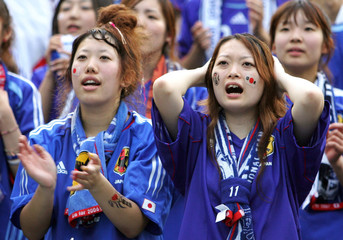 Japanese soccer fans react to Brazil's goal as they watch World Cup match on television screen in Saitama