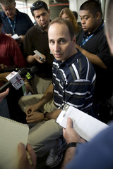 Yankees general manager Cashman talks with reporters outside the clubhouse before a MLB spring training exhibition game in Tampa