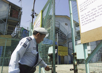 NEPALESE GUARD CLOSES GATE OF PILLAR POINT CAMP IN HONG KONG.