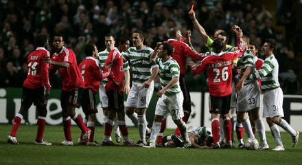 Players from both teams react as Benfica's Binya is sent off after tackle on Celtic's Brown during Champions League match in Glasgow