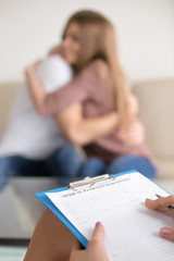 Close up of female psychotherapist holding clipboard, filling information about patients while couple embracing on couch in the background, doctor making notes in medical card in psychologists office