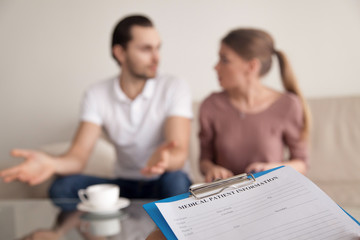 Young couple arguing on consultation with psychologist, unhappy marriage and constant domestic quarrels, marital discord. Consulting family relationships expert, focus on female hand with clipboard