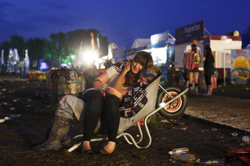 A couple cuddle in a wheelbarrow in the early hours of the morning at the end of Glastonbury Festival 2009 in south west England