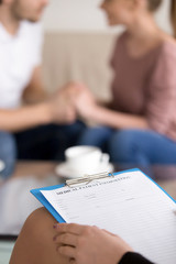 Couple counselling and successful therapy for families having problems in relationships. Close up of female psychologist holding clipboard with happy husband and wife in the background