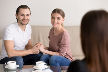 Happy young couple hold each other s hands listening to female agent, planning wedding, consulting investment advisor, hearing good news, casual marriage registration, buying real estate