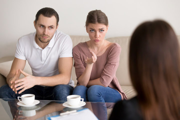Portrait of beautiful serious couple sitting on couch and talking to psychologist. Young woman telling specialist about family problems, her husband sitting next to wife and listening attentively