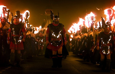 Jarl squad members gather to watch the burning of a viking long ship during the Up Helly AA festival..