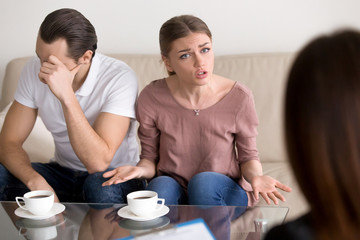 Portrait of unhappy couple consulting marriage counselor or family psychologist. Young emotional woman telling specialist about problems, her husband sitting next to wife frustrated and depressed