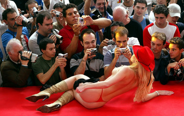 Spectators film with videocameras and take pictures as an actress performs a striptease in the main ..