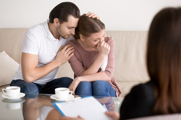 Couple counseling. Upset crying young woman having emotional breakdown, wiping tears, loving boyfriend trying to comfort girlfriend embracing her, husband consoling depressed wife at the psychologist