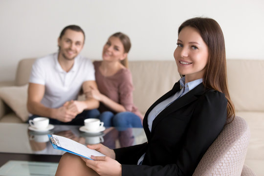 Portrait of smiling female psychologist, professional realtor or advisor consulting young happy family couple holding clipboard looking at camera. Financial advice, real estate agency, wedding planner