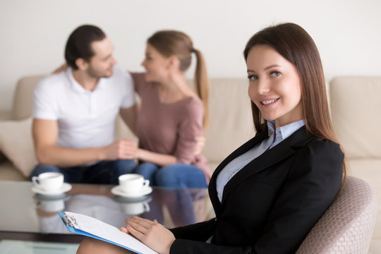 Portrait of cheerful smiling female wedding planner with clipboard looking at camera, young embracing couple sitting in the background. Real estate agent or financial advisor consulting happy family