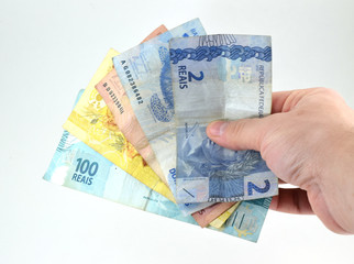 Hand holding Brazilian currency bills (real and reais) isolated, white background