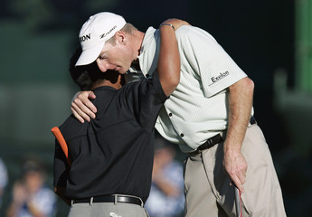 Sixteen year old amateur Tadd Fujikawa of the U.S. gets a hug from Jim Furyk after they finished the final round of the Sony Open golf tournament together in Honolulu