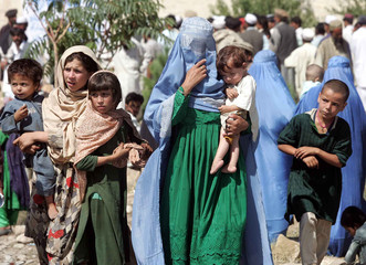 Afghan refugee families walk as they depart from a refugee camp in Parachinar.