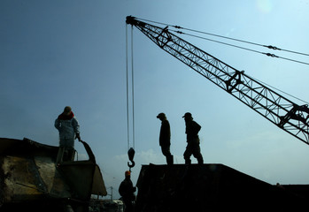 INDONESIAN WORKERS STAND NEAR A CRANE AS THEY BREAK UP A SHIP IN JAKARTA.