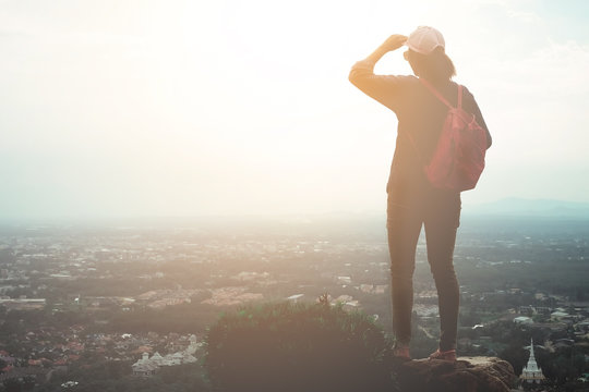 Traveling women are standing on the top of the hill overlooking the city of the evening