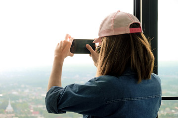 Traveling women are using a smartphone to capture the image of the city.
