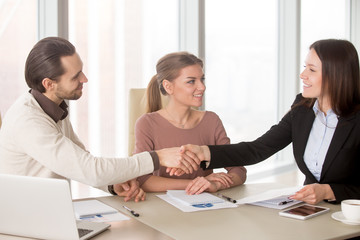 Young smiling businessman and businesswoman shaking hands over the table on meeting. Negotiating about business partnership, greeting new team member, nice to meet you, working on project together