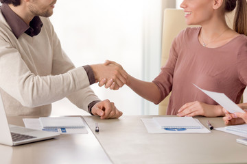 Young successful male and female partners greeting, forming a group for collaborative work on a project, shaking hands and smiling, happy to start negotiations, welcoming new business team member