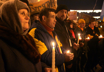 Supporters of Ukrainian opposition leader Yushchenko hold candles during funeral in central Kiev.