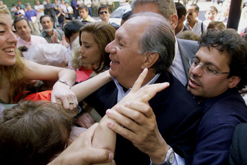 Presidential candidate and Socialist Ricardo Lagos (C), accompanied by his son Ricardo (L), greets s..