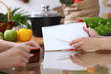 Human hands pointing into note book with copy space area. Two woman making menu in the kitchen, closeup. Cooking and friendship concept