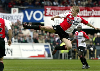 Dirk Kuijt of Feyenoord Rotterdam (R) performs a karate kick to reach the ball during the Dutch socc..