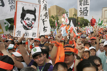 A protester holding a portrait of Taiwan's President Ma Ying-jeou with devil horns takes part in a rally in Taipei