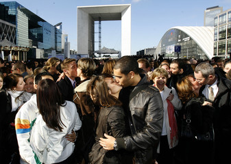 Participants simultaneously kiss to gain entry into the Guinness World Records during Guinness World Records Day at La Defense near Paris