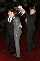 """Director Stephan Elliott waves Fizz the dog above heads of actors Firth and Barnes as they arrive for the premiere of """"Easy Virtue"""" in Leicester Square, London"""