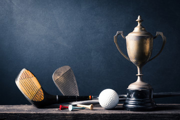 still life photography : golf club and golf ball and tee with old champion trophy on old wood against space of art dark background