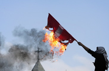 A masked Palestinian holds a burning Danish flag in front of the Church of Nativity in the West Bank..
