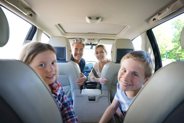 Happy family inside car leaving for vacation