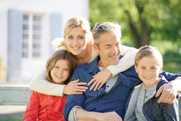 Portrait of happy family of four sitting on bench