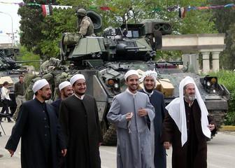 ARAB IRAQIS WALK IN FRONT OF U.S. ARMOURED PERSONNEL CARRIER IN KIRKUK.