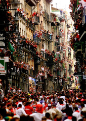 "Bull runners lead the pack of fighting bulls on ""Estafeta"" street in central Pamplona as onlookers w.."