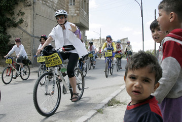 Members of Follow the Women Foundation ride bicycles past Iraqi children during tour in Amman
