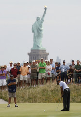 New York's Statue of Liberty is seen in the background as Tiger Woods of the U.S. putts on the second hole during first round play at The Barclays golf tournament