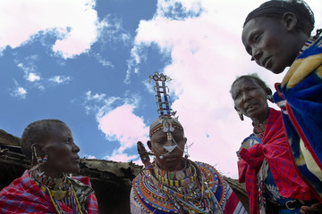 Maasai bride, wearing traditional bead necklaces, is accompanied by her relatives in Olepolos village
