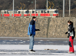A young couple enjoy skating on the frozen Vltava river in Prague.