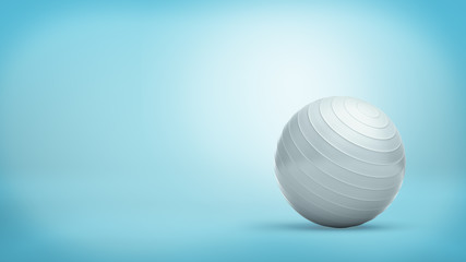 A silver ridged balance ball made of shining rubber placed on blue background.
