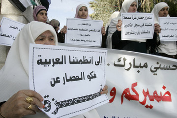 Women hold up placards during a demonstration in Amman