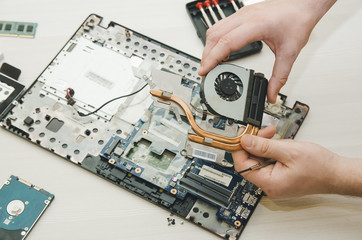 Repair laptops, close-up of hands and dismantled old computer.