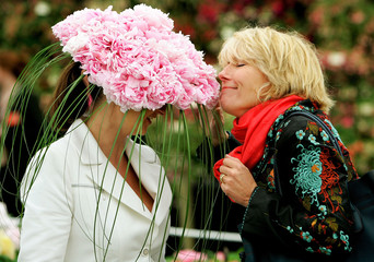 British actress Thompson smells at hat worn and designed by artist Lass at Chelsea Flower Show in London