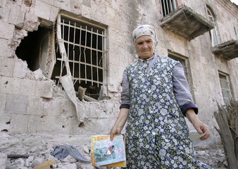 Nunu Alghonashvili, 72, stands outside her destroyed house in Gori